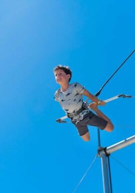 boy flies on trapeze at Club Med